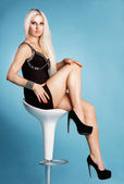 Sexy young blonde in short black dress and high heels — Stock Photo