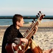 Stock Photo: Mplays sitar on beach