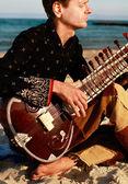 Plays sitar near the beach — Stock Photo