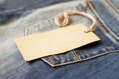 Blank paper label with string on jeans — Stock fotografie