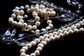 Pearls and crystals on black background — Stock Photo