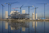 Construction cranes building a waterside office development — Стоковое фото