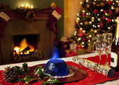 Christmas Pudding and Festive Fireplace — Stock Photo