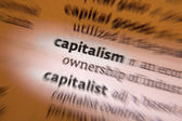 Capitalism is an economic and political system in which a country's trade and industry are controlled by private owners for profit, rather than by the state. — Stock Photo