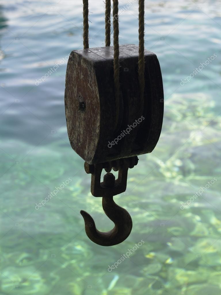 Hook hanging over shallow water on a dockside. — Stock Photo #18334543