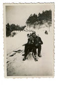 Winter holidays - man and woman on a toboggan — Stock Photo
