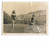 Friends - Two young women in bikini (walking through the meadow) — Stok fotoğraf