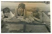 Friends - three young women in a blanket (sunbathing by the water) — Стоковое фото