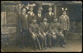 Group of men (and soldiers) in front of timber (probably weddings) — Stockfoto
