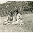 Girls sitting on a meadow. — Stock Photo