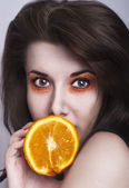 Young beautiful girl posing with orange — Stock Photo