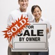 Stock Photo: Attractive couple with sold sign