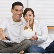 Attractive Asian Couple Eating Popcorn in Bed — Stock Photo
