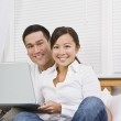 Asian couple with laptop — Stock Photo