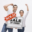 Couple with FSBO home sold sign. — Stock Photo