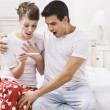 Surprised couple looking at a pregnancy test — Stock Photo