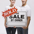 Couple Holding For Sale By Owners Sign - Stock Photo