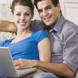 Happy Couple Using Laptop - Stock Photo