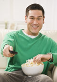 Attractive Asian Man with Popcorn and Remote Control — Stock Photo