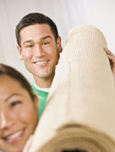 Attractive Couple with Roll of Carpet — Stock Photo