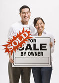 Attractive couple with sold sign — Stock Photo
