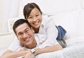 Heureux couple posant sur un lit — Photo
