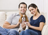Couple with dog on their lap in their living room. — Stock Photo