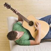 Homem tocando guitarra no divã. — Fotografia Stock