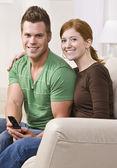 Séduisante jeune couple assis sur le canapé — Photo