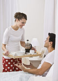 Attractive woman serving breakfast in bed. — Stock Photo