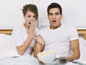 Surprised Young Couple Watching TV — Stock Photo
