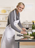 Attractive woman slicing cucumber — Stock Photo