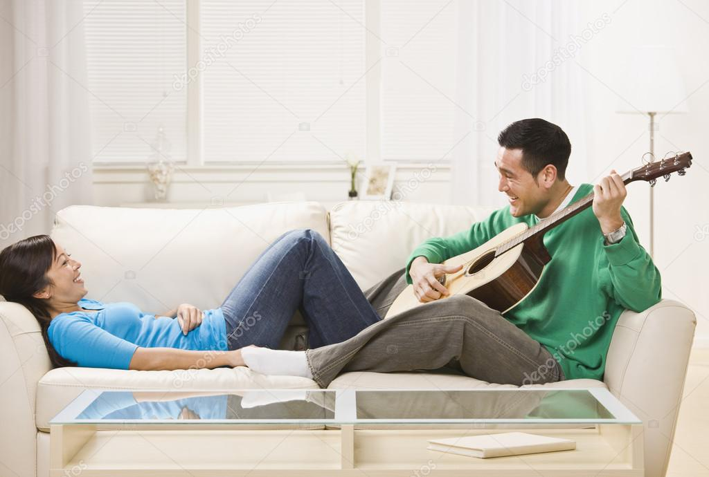 Asian couple on couch playing guitar. Man serenading the woman. Horizontal — Stock Photo #18762481