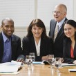 Four business workers smiling — Stock Photo