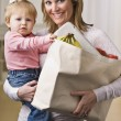 Mother Holding Daughter and Groceries — Stockfoto