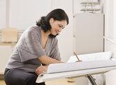 Femme travaillant sur plansbelle femme hispanique d'écriture — Photo
