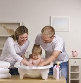 Lyckliga föräldrar bad baby — Stockfoto