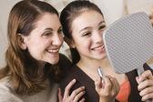 微笑母亲和女儿与口红,看着镜子 — 图库照片