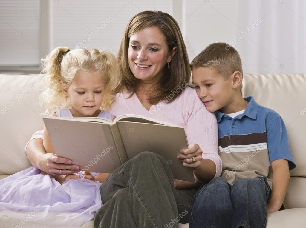 A happy-looking mother reading to her son and daughter in their home.  Horizontally framed shot. — Stock Photo #18778187