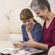 Stock Photo: Grandmother and Granddaughter Looking at Photos