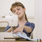 Girl on Sewing Machine — Stock Photo
