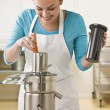 图库照片: Woman Using Juicer