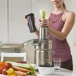 Attractive woman using juicer — Stockfoto