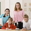 Teacher, students and microscope in classroom — Stock Photo