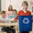 Student carrying recycling bin — Stock Photo