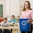 Teacher holding recycling bin — Stock Photo