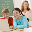 Girls using laptop in classroom — Stock Photo