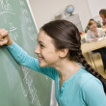 Student writing on blackboard — Stock Photo