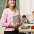 Teacher standing with notebook in classroom — Stock Photo