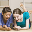 Teenage girls text messaging on cell phone - Stock Photo